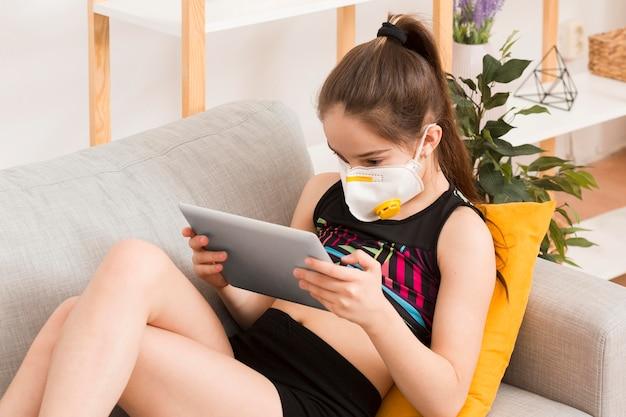 Menina no sofá com máscara usando tablet