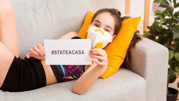 Menina no sofá com máscara