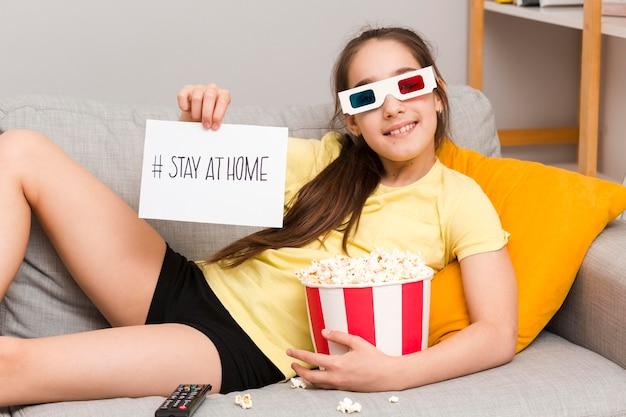 Menina no sofá com óculos 3d comendo pipoca