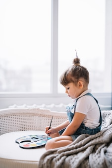 Menina no sofá com paleta aquarelle