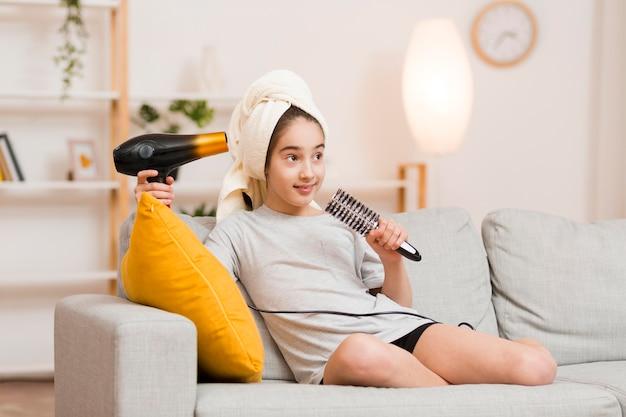 Menina no sofá com secador de cabelo e escova