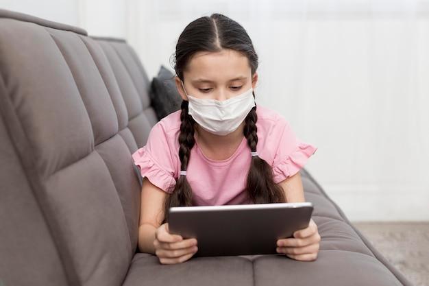 Menina no sofá usando máscara Foto gratuita