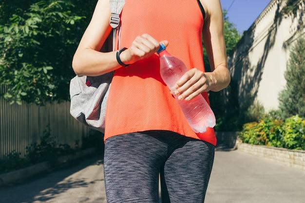 Menina no sportswear com mochila segurando uma garrafa de água fria