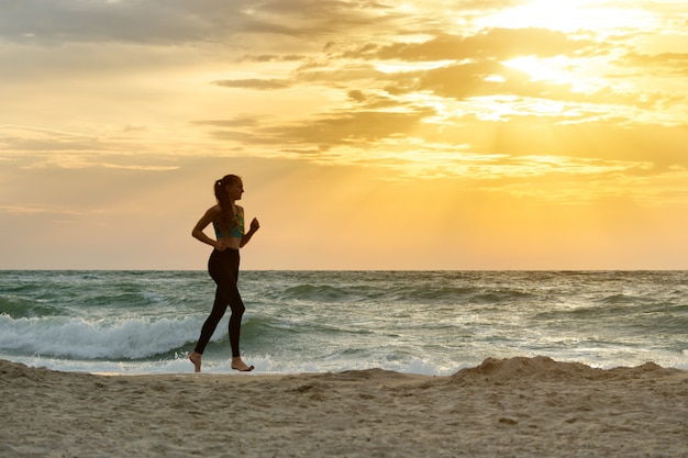 Menina no sportswear correndo ao longo da linha de surf. de manhã cedo.