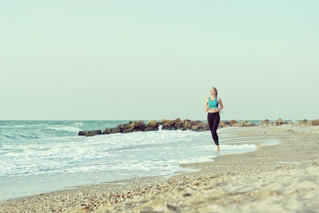 Menina no sportswear correndo ao longo da linha de surf.