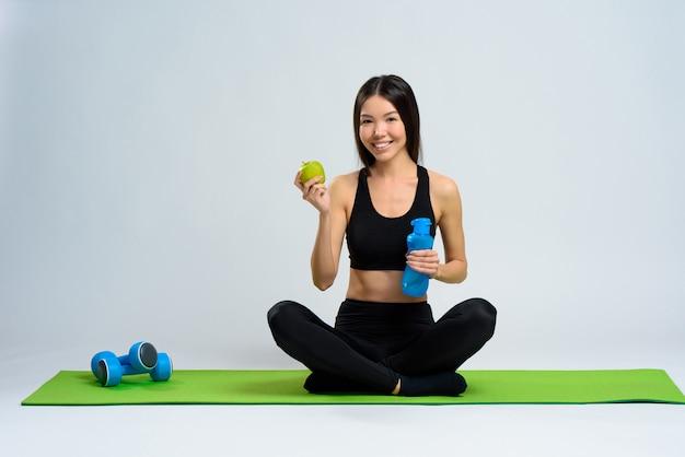 Menina no tapete de ginásio com garrafa de água e maçã.