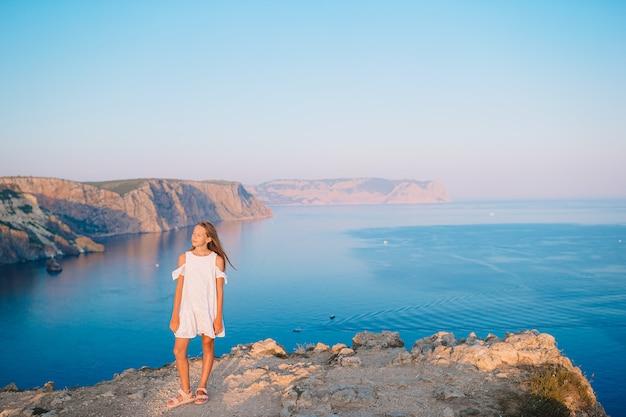 Menina no topo de uma montanha, apreciando a vista do vale antes do pôr do sol