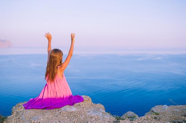Menina no topo de uma montanha apreciando a vista do vale antes do pôr do sol