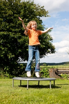 Menina no trampolim no jardim