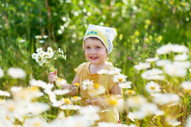 Menina no verão planta de camomila