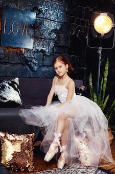 Menina no vestido de bola e nas sapatas brancas, cabelo vermelho bonito. jovem atriz de teatro