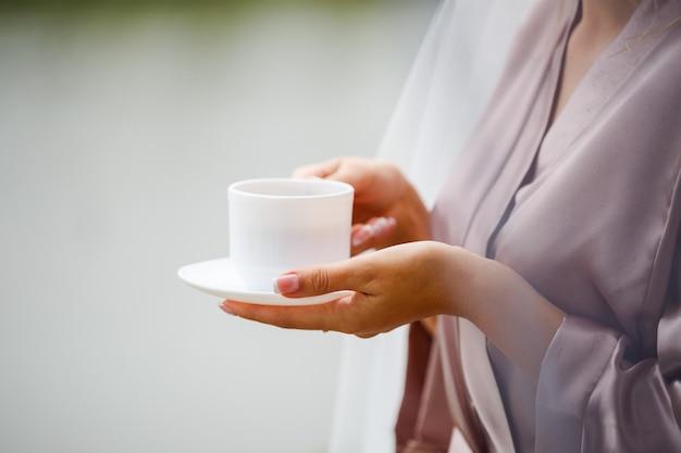 Menina noiva bebe café na manhã do casamento