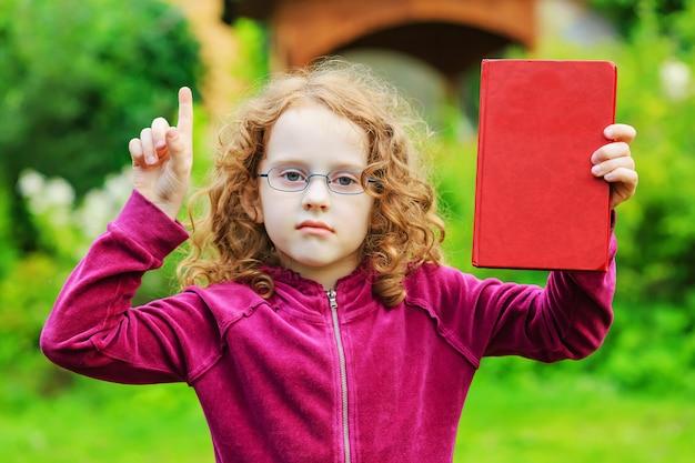 Menina nos monóculos com livro e dedo vermelhos acima.