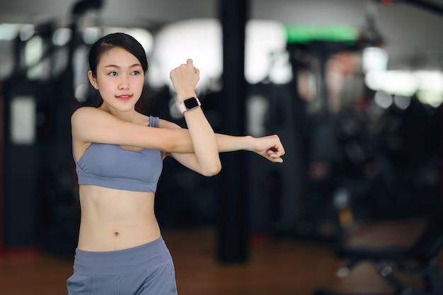 Menina nova da aptidão no sportswear à moda que aquece antes de treinar na ginástica