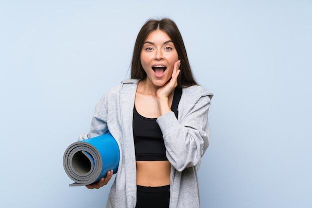 Menina nova do esporte com esteira sobre a parede azul isolada com surpresa e expressão facial chocada