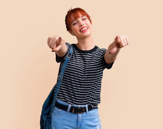 Menina nova do ruivo do estudante que aponta com o dedo em alguém e que ri muito.