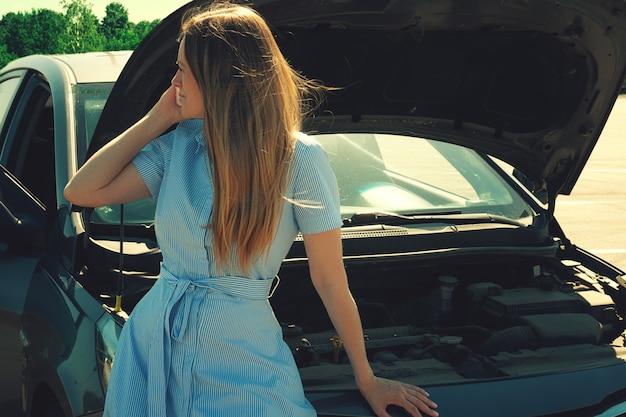 Menina nova e bonita perto de um carro quebrado com uma capa aberta. problemas com o carro, não inicia, não funciona.