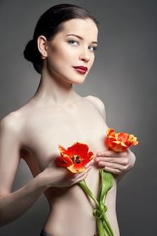 Menina nua nua com flores de tulipas na mão