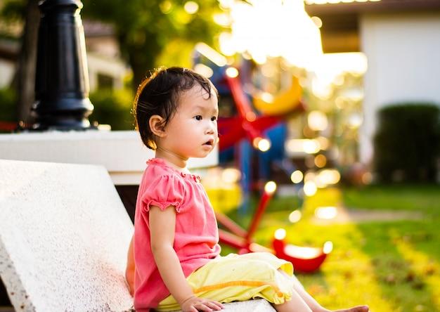 Menina o sente-se o campo de jogos da cadeira. criança brincando ao ar livre no verão.