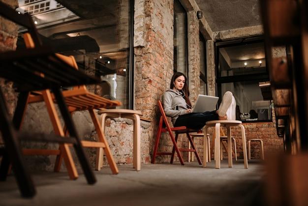 Menina ocasional que relaxa usando o portátil no terraço com as paredes de tijolo velhas.
