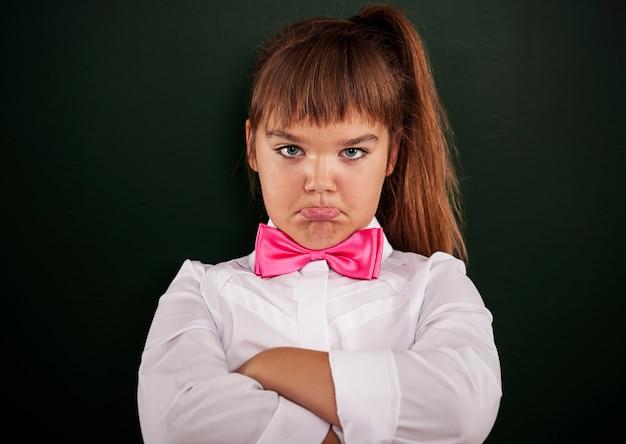 Menina ofendida com gravata borboleta rosa