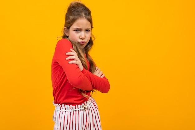 Menina ofendida cruzou os braços em um fundo amarelo com espaço de cópia.