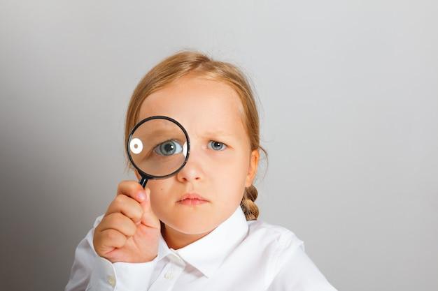 Menina olha através de uma lupa com interesse.
