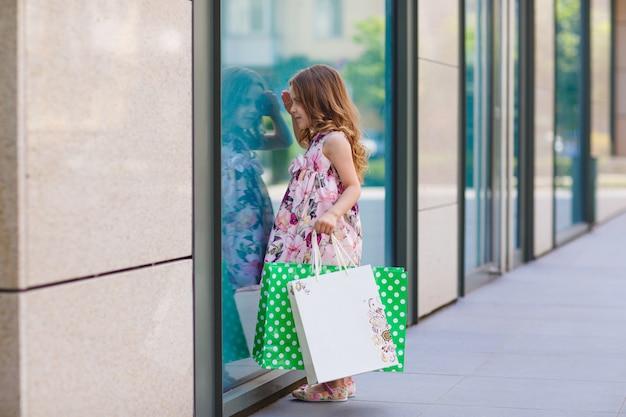 Menina olha para a janela perto do shopping.