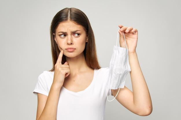 Menina olha para a máscara médica com um dedo no rosto camiseta branca