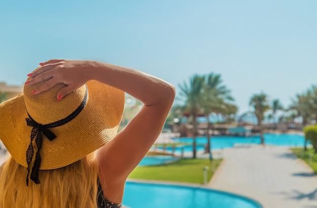 Menina olha para a piscina e o mar
