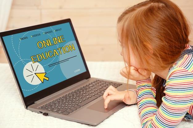 Menina olha para o computador. educação online está escrita no monitor do computador.