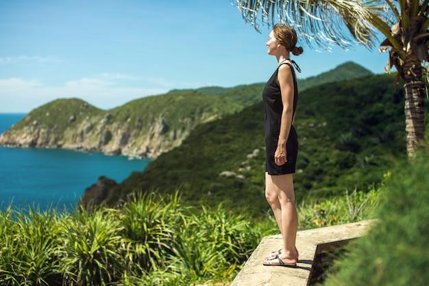 Menina olha para o panorama das montanhas à beira-mar