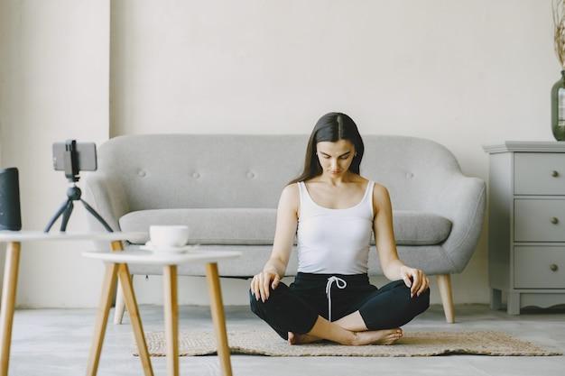 Menina olha para o telefone. amassando yogi. mulher em casa com uma roupa esportiva.