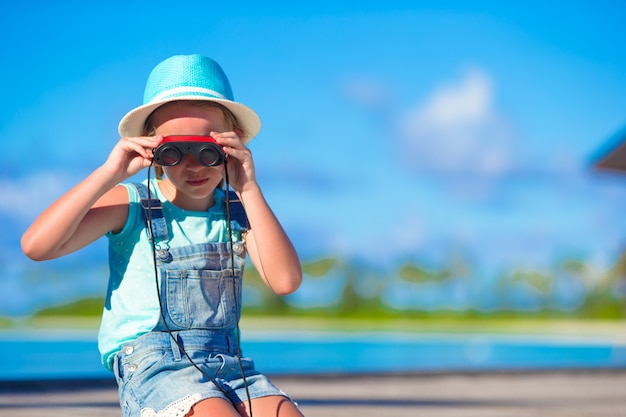 Menina olhando através de binóculos em dia de sol durante as férias de verão Foto Premium
