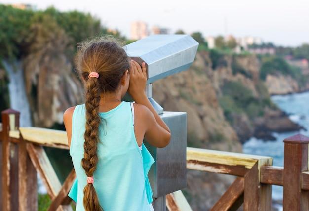 Menina olhando através de binóculos para o mar mediterrâneo
