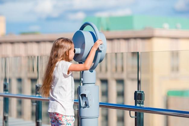 Menina olhando binóculo a moedas no terraço com bela vista