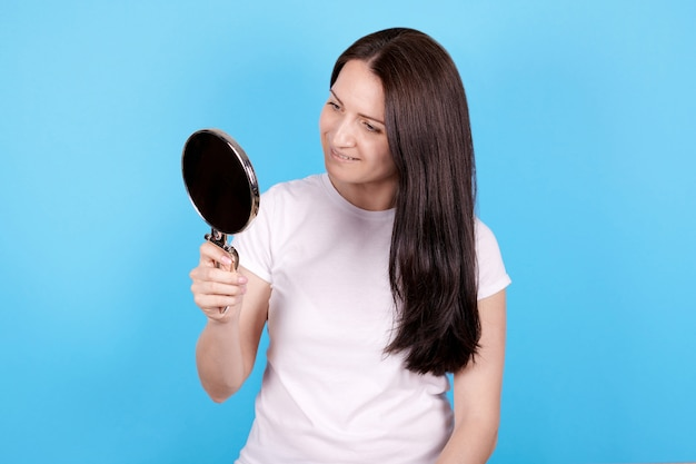 Menina olhando no espelho e sorrindo. isolado em fundo azul