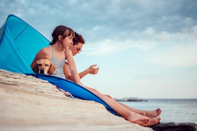 Menina olhando o pôr do sol enquanto está sentado na barraca de praia com mãe e cachorro