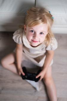 Menina olhando para a câmera brincando com joystick