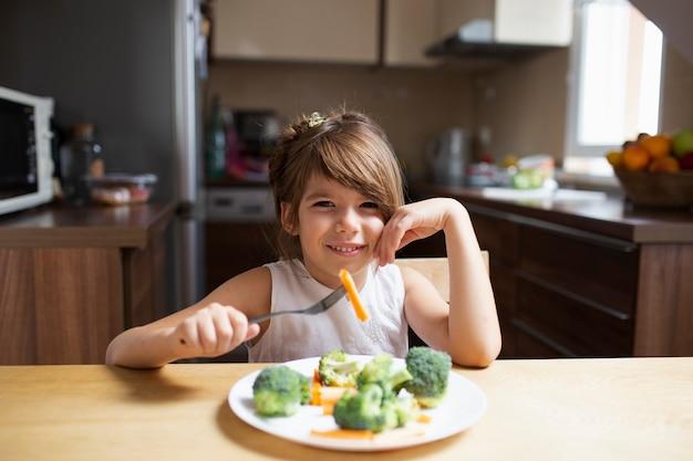 Menina olhando para a câmera enquanto come legumes