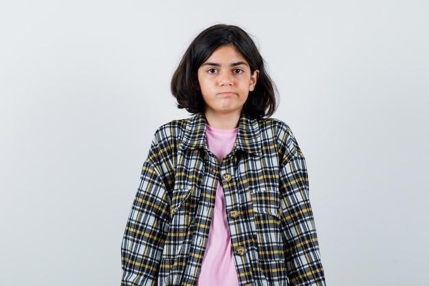 Menina olhando para a câmera na camisa, jaqueta e olhando calma, vista frontal.