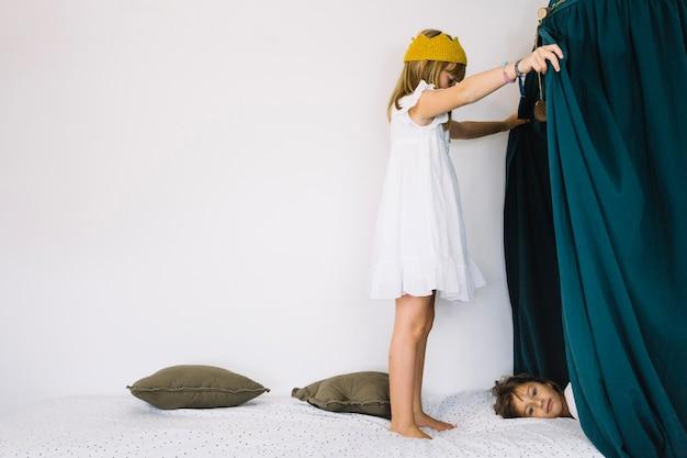 Menina olhando para a irmã atrás das cortinas