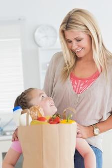 Menina olhando para a mãe depois de fazer compras