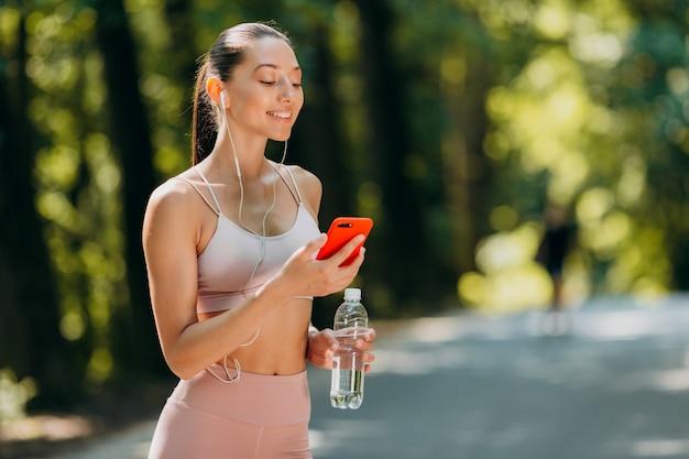 Menina olhando para a tela no smartphone e ouvir música em fones de ouvido ao ar livre.