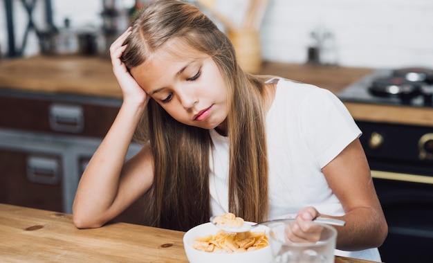 Menina olhando para a tigela com cereais
