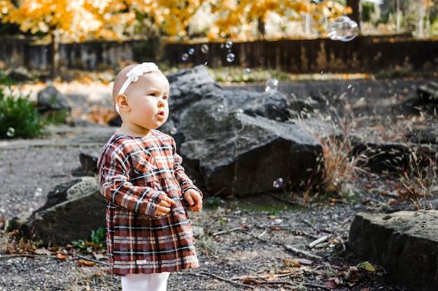 Menina olhando para bolhas de sabão, no parque outono