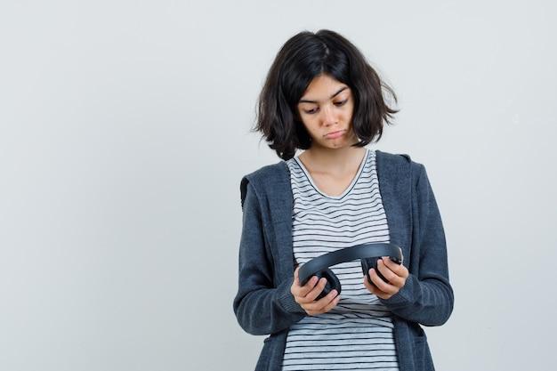 Menina olhando para fones de ouvido em t-shirt, jaqueta e olhando pensativa.