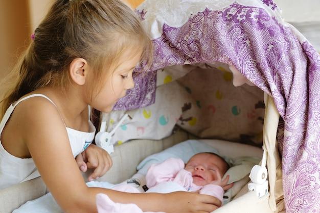 Menina olhando para o bebê recém-nascido no berço
