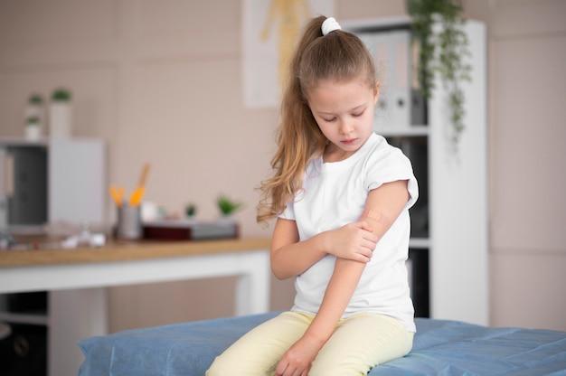 Menina olhando para o braço dela depois de ser vacinada
