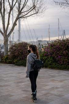 Menina olhando para o horizonte com patins no calçadão à beira-mar em palma de maiorca, espanha
